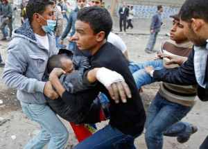 Carrying the injured to an ambulance in Tahrir Square